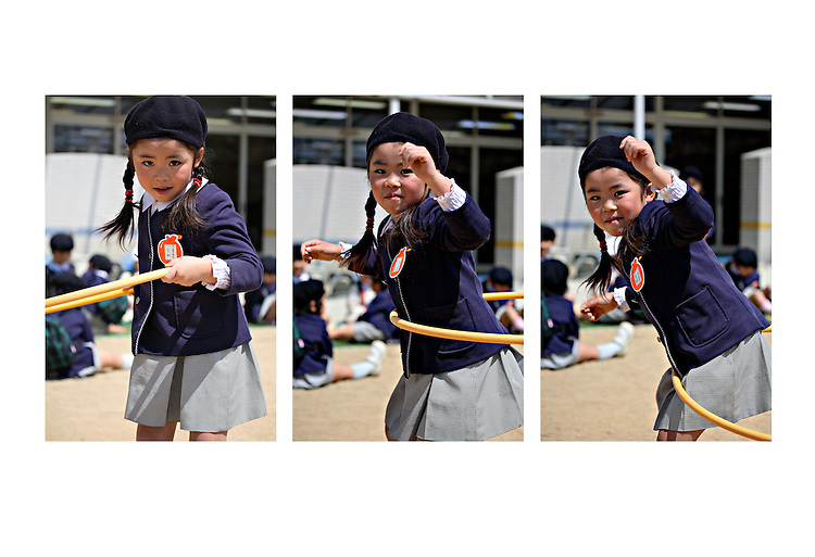 A young Japanese girl plays with a hula hoop