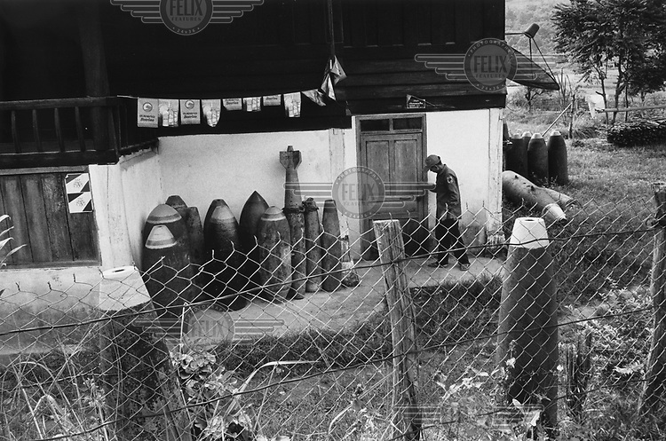 A bomb dealer outside his home where he has stored a large variety of defused munitions. The bombs are made safe by the army and the explosives removed and sold to construction companies. The dealer then transports the bomb casings to Xieng Khouang and Vientiane to sell to restaurants and hotels for use as ironic decorations. More than two million tonnes of ordnance was dropped over Laos ruring the Second Indo-China War, an estimated 30 per cent of which did not explode on impact. UXO still affects more than 25 per cent of Lao villages