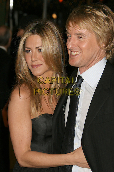 "JENNIFER ANISTON & OWEN WILSON.""Marley & Me"" Los Angeles Premiere held at the Mann Village Theater, Westwood, California, USA..December 11th, 2008.half length black grey gray strapless silk satin top skirt dress frills ruffled ruffles blue tie white shirt suit jacket hand on chest stomach .CAP/ADM/MJ.©Michael Jade/AdMedia/Capital Pictures."
