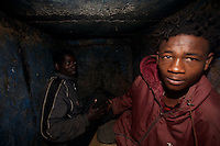 Wndemag ( on right ) and Tsegalem, homeless boys from  the rural areas weak up in the hole where they live to go to work in the fruit market in Addis Ababa, Ethiopia, on Thursday August 24 2006.Tsegalem, 19 and Wendemag, 17 arrived in Addis Ababa seven months ago filled with hope to find a decent job and a new life. At least that was what people from their village told them. Once in the city they had nowhere to go and no idea on how to make a living..Their home became a sewage hole in the only place in town were they could earn a few pennies a day: the fruit market..? I want to go home? says one of them. ? This is no life, we live like rats. As soon as I put together enough money for my bus ticket I will leave this place?. .?We both work carrying cases at the market for 5 birr a day?, about 70 USD cents..Trucks and buses rumble in the depth of their shelter. They sleep close to each other in the attempt of defeating the rainy season?s cold nights.?We constantly get harassed by the police. They often beat us up just because we are in this situation. We keep on getting blamed for everything that happens in the market?.These boys though find strength in one another: ? we have to take care of each other, it?s our only way to make it?. And food? ?well?, says Wendemag, ? fortunately that hotel owner over their lets us eat the client?s leftovers?.