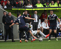 Filip Kiss fouls Kenny McLean watched by Melvin De Leeuw as Ross County Manager Derek Adams (furthest left)  shouts orders in the St Mirren v Ross County Scottish Professional Football League Premiership match played at St Mirren Park, Paisley on 3.5.14.