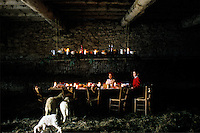 Two little girls watch over the lambs that wander around the festive candlelit table in this hay-strewn barn