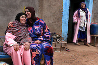 "Khina Boujnoui and her daughter, Fatima, share a moment of affection outside the family's home in Tamda, Morocco. The women are part of a traditional Berber family that has been weaving for generations. ""Weaving is the way we express ourselves,"" says Fatima whose own daughter wants to attend university and has been less enthusiastic about the family's tradition."