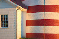 This close-up view of the West Quoddy Head Light in Lubec, Maine, highlighted by early morning light, is a study in contrasts between the curved, brick, candy-striped light tower and the angular, shingle-covered, all white facade of the adjacent building.