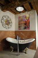 An artwork of Mozart features large on the wall of this ensuite bathroom at the Am Dom boutique hotel in Salzburg, the composer's birthplace