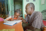 Abdel Karim, a refugee from the Darfur region of Sudan, helps his 7-year old daughter Dana with her homework in their apartment in Cairo, Egypt. Karim and his wife have both taken adult education classes provided by St. Andrew's Refugee Services, which is supported by Church World Service.
