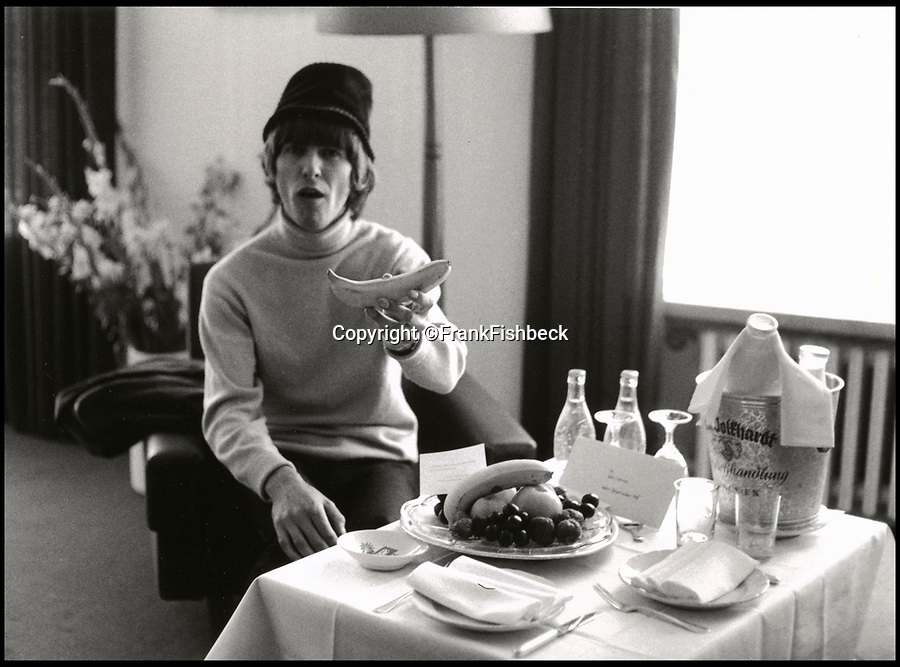 BNPS.co.uk (01202 558833)<br /> Pic: FrankFischbeck/Spink/BNPS<br /> <br /> Harrison offers Fishbeck a banana at their Munich hotel.<br /> <br /> Unseen photos of the fab four touring Germany in 1966 are being sold showing the group just before they ditched the suits, gave up touring and embraced the flower power revolution.<br /> <br /> The candid snaps were taken by enterprising photographer Frank Fishbeck in Munich and Essen in June 1966 after he had managed to <br /> follow them into their Munich hotel and they invited him to their concert.