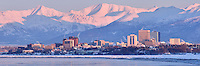 The city of Anchorage, Alaska is bathed in pink light as the sun sets on a bitterly cold winter day.