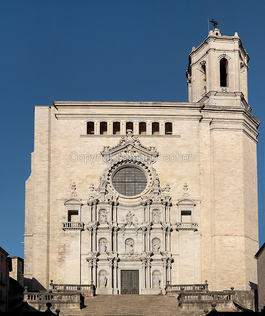 Baroque facade of the Santa Maria Cathedral or Cathedral of St Mary of Girona, in Girona, situated at the confluence of the rivers Ter, Onyar, Galligants and Guell, Catalonia, Spain. Here we see the Baroque facade, begun in 1606 and completed in 1961, with its sculptures decorating the 3 orders of the facade made by local sculptors in the 1960s, and the new octagonal bell tower, begun in 1590 and completed in the 18th century, which houses 6 bells. A staircase of 90 steps dating to 1607 leads up to this entrance. The cathedral was begun in the 11th century in Romanesque style, and later continued in the 14th century in Catalan Gothic style, redesigned by Pere Sacoma in 1312 and built by the school of Mallorcan architect Jaume Fabre. Of the original Romanesque building only the 12th century cloister and a bell tower remain. The cathedral was completed in the 18th century. Picture by Manuel Cohen