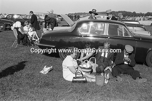Epsom Downs, Surrey. 1970<br /> Top hat and tails, cloth cap and pipe, its Derby Day. Londoners down for a day at the races, enjoy an alfresco picnic in the car park, sheltered from the breeze and warm in the sun, they lean up against a returning race goers Jaguar.