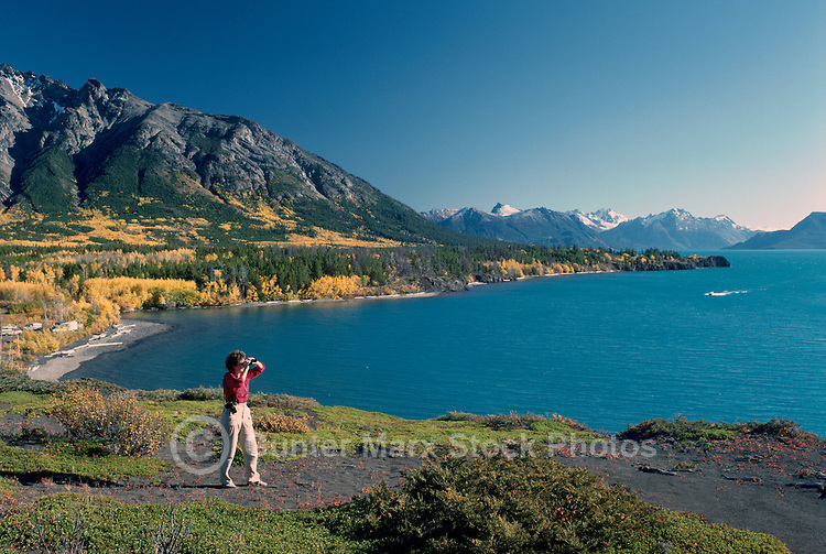 Chilko Lake and Coast Mountains in Ts'yl-os Provincial Park, Cariboo Chilcotin Coast Region, BC,  British Columbia, Canada - Woman looking through Binoculars, Autumn / Fall (Model Released)