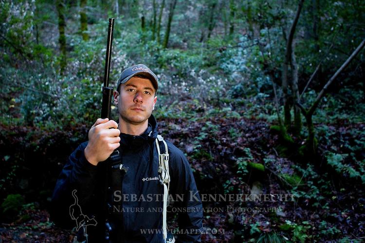 Mountain Lion (Puma concolor) biologist, Sean McCain, holding darting rifle during attempt to re-collar a male puma, Santa Cruz Puma Project, Uvas Canyon County Park, Santa Cruz Mountains, California