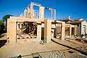 A wooden construction frame of a large two-story house. Large amounts of wood and other raw materials are being used to build this new house on a lot where a single-story home was demolished. Cupertino, California, USA