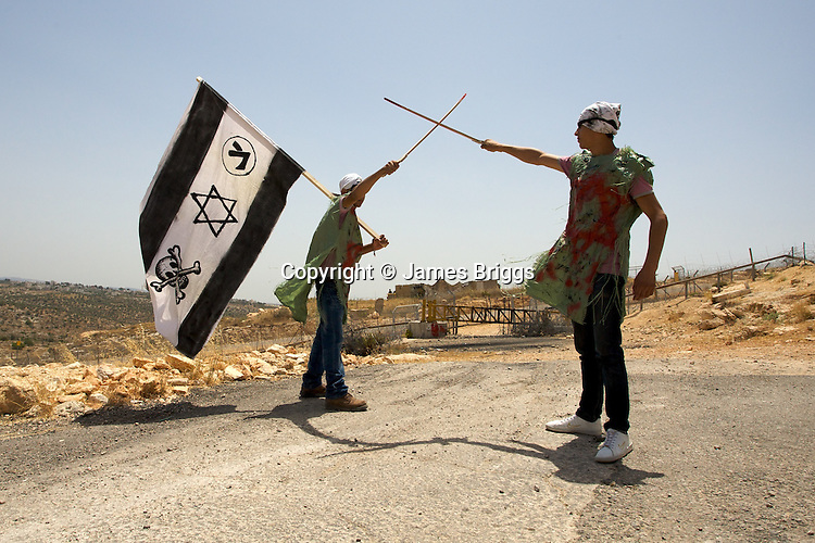 Palestinians from the village of Bil'in mock nearby Israeli soldiers by dressing up as pirates in reference to the botched raid on the Mavi Marmara aid ship in international waters, during the villager's weekly protest against the controversial West Bank barrier, near Ramallah on 04/06/2010.
