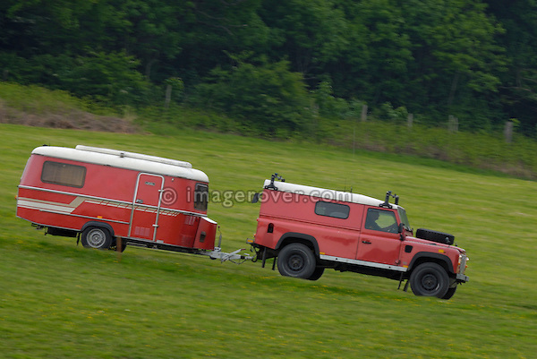 Red Land Rover Defender 110 Hard Top towing a matching red caravan to the ALRC National 2008. The Association of Land Rover Clubs (ALRC) National Rallye is the biggest annual motor sport oriented Land Rover event and was hosted 2008 by the Midland Rover Owners Club at Eastnor Castle in Herefordshire, UK, 22 - 27 May 2008. --- No releases available. Automotive trademarks are the property of the trademark holder, authorization may be needed for some uses.