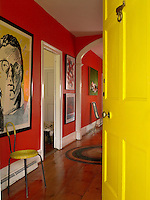 The bright yellow-painted front door with its whale door knocker opens into the entrance hallway with wide plank floorboards and walls of Chili Pepper red