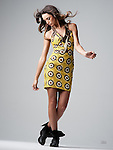 Beautiful brunette fashion model in yellow dress and black boots