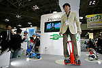 DECEMBER 10, 2009 - TOKYO - JAPAN: Hiroyuki Murakami, Toyota Motor Assistant Manager, displays a proyotype model of personal transport assistance robot 'Winglet' during the Eco-Product 2009 in Tokyo Big Sight. Some 700 exhibitors introduce their consumer goods, industrial materials, energies, finance and various services during three days. New environmental technologies and services that aim to change conventional wisdom, and new business models that aim to solve specific problems, including company coalitions and regional cooperation are displaying. In addition, 20,000 students in the Kanto Region as a school activity, and families can experience the low-carbon lifestyle of the near-future. 180,000 visitors are expected to attend (photo by Laurent Benchana/Nippon News)...