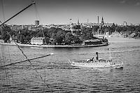 Ångbåten Storskär går ut framför Kastellholmen i Stockholm i svartvitt.
