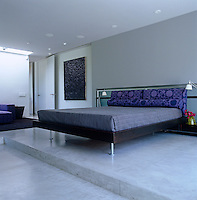 The bed in the master bedroom stands on a platform of polished concrete
