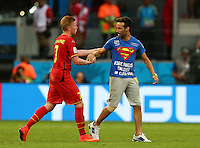 A pitch invader shakes hands with Kevin De Bruyne of Belgium