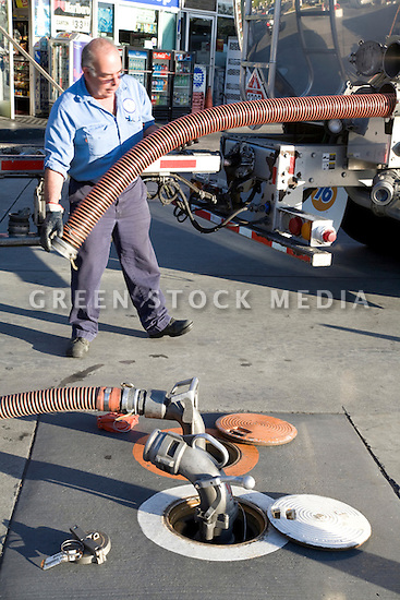 A gas truck driver storing a gas hose after delivering an underground tank. Mountain View, California, USA
