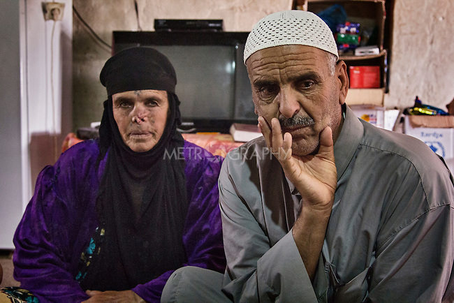 23/06/2015 -- Dibaga-Makhmur-, Iraq --  Muhammad Jasim 52 Y.O. and Mona Ibrahim Hussein 70 y.o. from Jarallah village sit in their new home at the chicken farm in Dibaga. Mona Ibrahim Hussein, who lost her nose from an infection and the surgery to repair it was unsuccessful, has seen two of her sons taken by the Kurdish Security forces into custody on suspicion of being affiliated to ISIS.