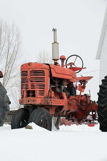 Old farm tractors sitting outside in the snow, used agricultural equipment on outside display in Pennsylvania, PA, USA.
