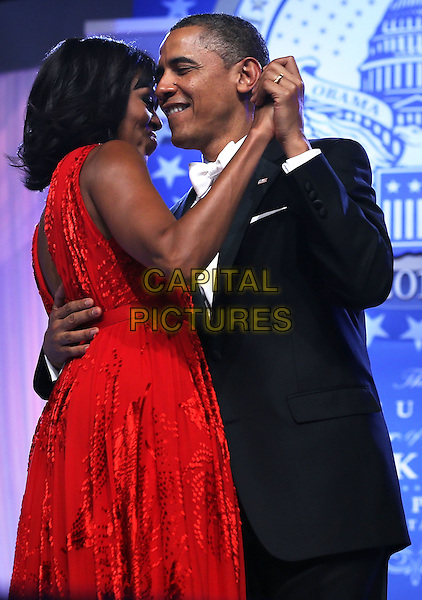 Michelle Obama & Barack Obama.2013 Inauguration Ball, Washinton D.C., USA..January 21st, 2013.half length black suit tuxedo red dress profile holding hands married husband wife dance dancing.CAP/ADM/CNP/AW.©Alex Wong/CNP/AdMedia/Capital Pictures.