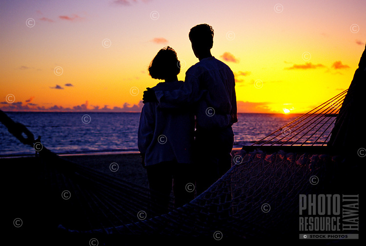 Couple hugging in front of a romantic sunrise beside a hammock at Kailua beach on Oahu
