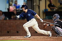 Mobile BayBears left fielder Zach Gibbons (14) follows through on a swing in front of catcher Brian Olson (30) during a game against the Chattanooga Lookouts on May 5, 2018 at Hank Aaron Stadium in Mobile, Alabama.  Chattanooga defeated Mobile 11-5.  (Mike Janes/Four Seam Images)