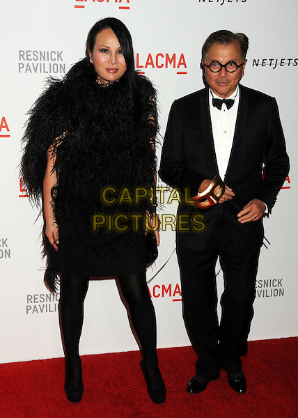 "EVA CHUN & MICHAEL CHOW .LACMA's ""The Unmasking"" of the Lynda & Stewart Resnick Exhibition Pavilion Opening Gala held at the Los Angeles County Museum of Art, - Los Angeles, California, USA, 25th September 2010..full length tuxedo tux fluffy feather dress feathers tights black bow tie glasses round frames .CAP/ADM/BP.©Byron Purvis/AdMedia/Capital Pictures."