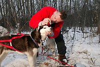 Dog musher Blake Matray tends to his dogs at the first checkpoint along the 2003 Iditarod trail in the village of Nenana.