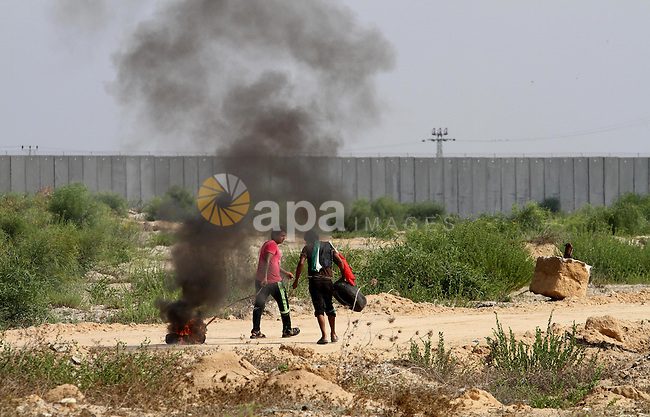 Palestinian protesters run for cover during clashes with Israeli security forces near the Erez border crossing between Israel and northern Gaza Strip on October 13, 2015. A wave of stabbings that hit Israel, Jerusalem and the West Bank this month along with violent protests in annexed east Jerusalem and the occupied West Bank, has led to warnings that a full-scale Palestinian uprising, or third intifada, could erupt. The unrest has also spread to the Gaza Strip, with clashes along the border in recent days leaving nine Palestinians dead from Israeli fire. Photo by Mohammed Asad