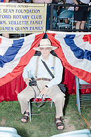 A man sits with a camera as he watches the 4th of July Parade in Amherst, New Hampshire, on Thu., July 4, 2019.