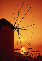 Windmills at sunset with ships in background Mykonos Greece.