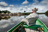 BRAZIL, Agua Boa, fly fisherman sitting in a boat on a tributary of the Amazon River, Agua Boa River and resort