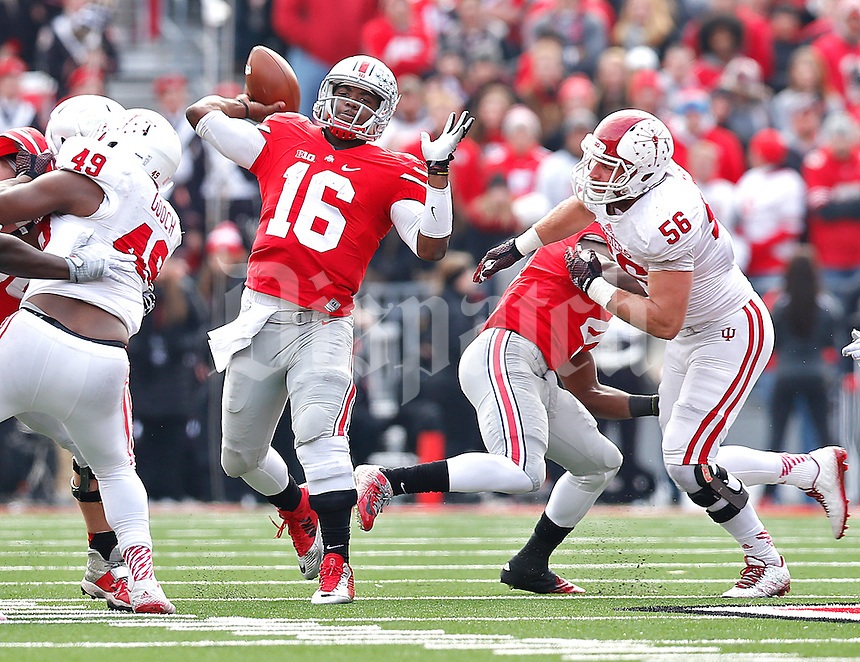 Ohio State Buckeyes quarterback J.T. Barrett (16) gets a pass off despite pressure by Indiana Hoosiers defensive end Nick Mangieri (56) and Indiana Hoosiers linebacker Greg Gooch (49) in the second half at Ohio Stadium on 22, 2014. (Chris Russell/Dispatch Photo)