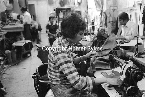 Asian men working making clothes garment workshop know as a sweatshop east London 1970s.