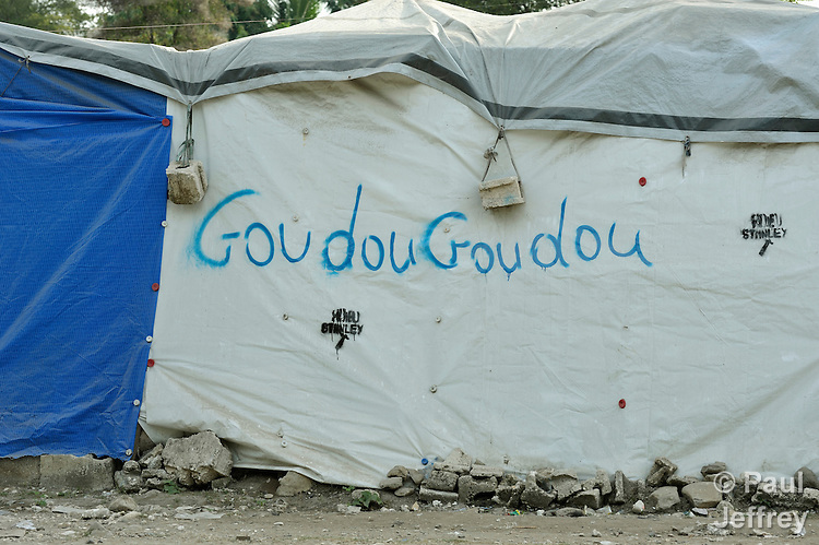 """GoudouGoudou,"" the Kreyol word that Haitians have come to call the earthquake that ravaged parts of their country in in January 2010, is scrawled on the wall of a tent in a camp in Grand-Goave, Haiti, where families left homeless by the quake continue to live. The word was derived from the sound that many recall the quake producing as their houses moved and collapsed. The ACT Alliance has supported families in this camp with a variety of services, and has rebuilt a school beside the tent city."