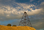 Headframe of the Fremont Mine, passing summer storm, oaks and golden hills at sunset, Amador County, Calif.