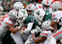 Ohio State Buckeyes linebacker Tuf Borland (32) and a slew of Buckeyes tackle Michigan State Spartans quarterback Brian Lewerke (14) during the first quarter of the NCAA football game at Spartan Stadium in East Lansing, Mich. on Nov. 10, 2018. [Adam Cairns/Dispatch]