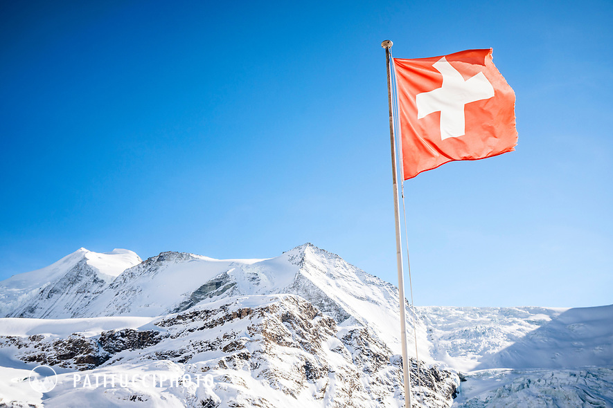 A Swiss flag hangs outside the Turtmann Hut with the Bishorn in the background. Switzerland