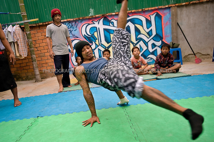 """11/15/2008--Phnom Penh, Cambodia..Tuy Sobil, 31, leads a Tiny Toones evening practice session in Phnom Penh's  Toul Tom Pong neighborhood...The Tiny Toones break dancing troupe was founded by Tuy Sobil, a.k.a. """"KK"""", a 31 yr old Cambodian and former gang member from Long Beach,  CA, who was deported from the United States in 2004.  Working out of the Toul Tom Pong neighborhood in Phnom Penh, the Tiny Toone's house runs a drop-in center  and community center for at-risk youth in Phnom Penh. Dance classes, as well as English lessons are offered at the center. The former gang member is Tuy Sobil, 30, who goes by the street name K.K. The boys are Cambodian street children he has taken under his wing as he teaches them the art he brought with him, break dancing, as well as his hard lessons in life..K.K. is not here because he wants to be. He is one of 189 Cambodians who have been banished from the United States in the past six years under a law that mandates deportations for noncitizens who commit felonies. Hundreds more are on a waiting list for deportation. Like most of the others, K.K. is a noncitizen only by a technicality. He was not an illegal immigrant. He was a refugee from Cambodia?s Khmer Rouge ?killing fields? who found a haven in the United States in 1980..He was an infant when he arrived. In fact, he was born in a refugee camp in Thailand and had never seen Cambodia before he was deported. But K.K.?s parents were simple farmers who failed to complete the citizenship process when they arrived..Like some children of poor immigrants, K.K. drifted to the streets, where he became a member of the Crips gang and a champion break dancer. It was only after he was convicted of armed robbery at 18 that he discovered that he was not a citizen...©2008  Stuart Isett. All rights reserved."""