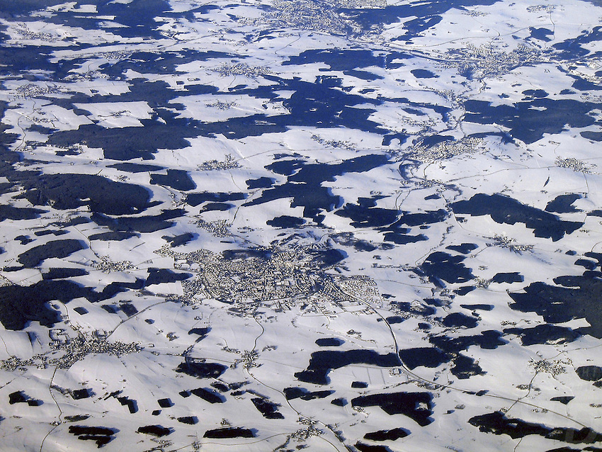 Aerial from a commercial jet, just about between the border Poland and Russia, snow covered fields during winter in February