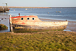 Abandoned old wooden boat rotting on the shoreline on the River Ore at Orford, Suffolk, England