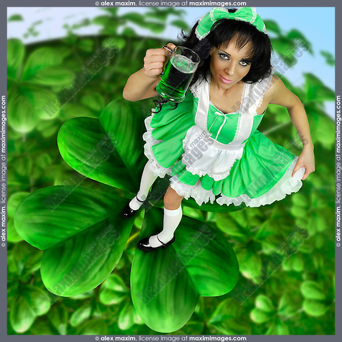 Lovely glamorous Irish girl in green dress holding a glass of green beer while standing on a four-leafed shamrock growing in a vivid green spring nature Saint Patricks Day celebration concept