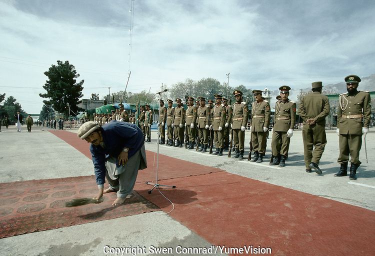 A man cleaning the red carpet in the centre of Charikar City before the arrival of President Borhan'udin Rabani, Warlord Ahmad Shah Massoud and General Abdul Quassim Fahim at a Mudjahedin parade, celebrating the liberation of Charikar from the communist army.