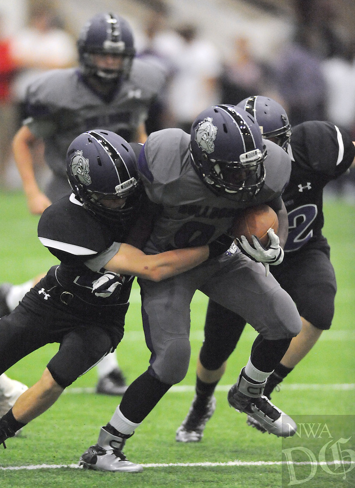 NWA Democrat-Gazette/ANDY SHUPE<br /> Terrance Rock (9) of Fayetteville is tackled by Will Litzinger (left) Friday, May 29, 2015, during the Bulldogs' annual Spring Game inside the school's indoor facility in Fayetteville. Visit nwadg.com/photos to see more photographs from the game.