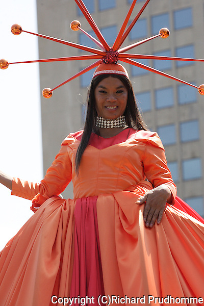 A large doll dressed in an orange dress participating in the Pride parade in Montreal